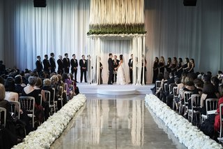 modern-jewish-indoor-ceremony-with-suspended-flowers-and-ribbons-forming-chuppahs