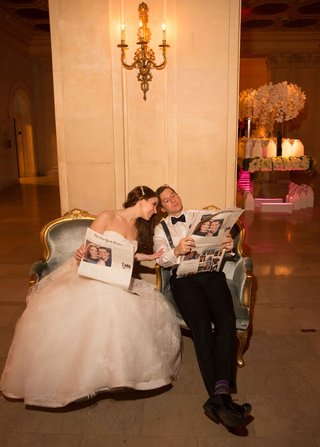 bride-in-strapless-wedding-dress-groom-in-bow-tie-suspenders-reading-special-edition-of-the-times