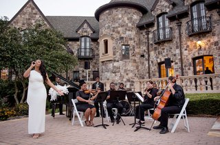 wedding-ceremony-on-lawn-of-private-estate-backyard-singer-in-white-dress-and-musicians-in-chairs