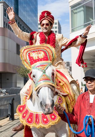 groom-in-traditional-indian-wedding-attire-before-ceremony-processional-on-decorated-horse