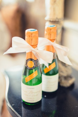 miniature-champagne-sparkling-wine-bottles-with-white-ribbon-for-guests-at-place-settings-french