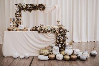 fall-wedding-ideas-sweetheart-table-arch-garland-gold-silver-white-pumpkins-candlesticks-draped