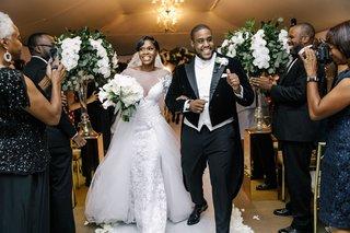 wedding-ceremony-jumping-the-broom-groom-in-long-tail-tuxedo-bride-in-overskirt-long-sleeve-dress