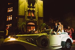 wedding-send-off-grand-exit-bride-and-groom-sitting-on-back-of-classic-car-outside-of-venue-wedding