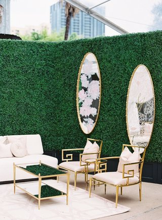 wedding reception cocktail hour white sofa gold chairs and table mirror on hedge wall