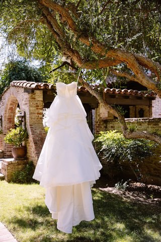 strapless-hayley-paige-wedding-dress-with-tiered-skirt-hung-on-tree-branch-at-hummingbird-nest-ranch