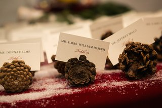 winter-wedding-with-escort-cards-in-pinecones-on-table-with-red-tablecloth-fake-snow