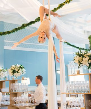 wedding-reception-special-silk-aerial-performer-at-reception-over-bar-and-server-greenery-garland