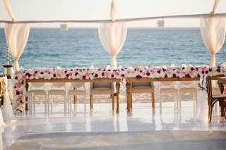 wood-tables-head-table-with-flower-runner-of-roses-in-shades-of-white-pink-and-burgundy-by-ocean