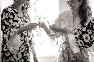black-and-white-photo-of-bride-in-robe-cheers-sipping-champagne-in-flutes-with-bridesmaids-in-robe