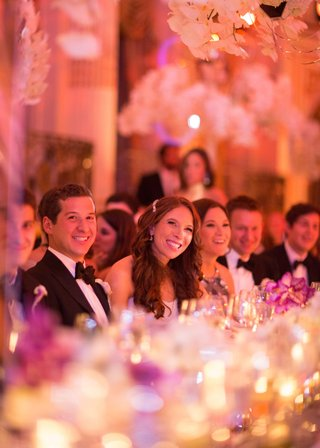 bride-and-groom-smiling-with-guests-at-head-table-during-reception-toasts-laughing-smiling