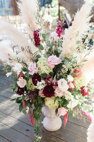 wedding-ceremony-flower-arrangement-with-wine-colored-flowers-and-pampas-grass
