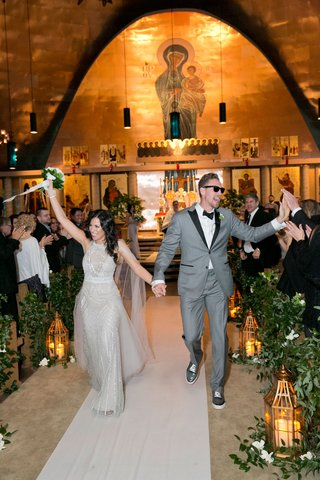bride-in-monique-lhuillier-wedding-dress-walking-down-aisle-holding-hands-with-hunter-pence-in-grey