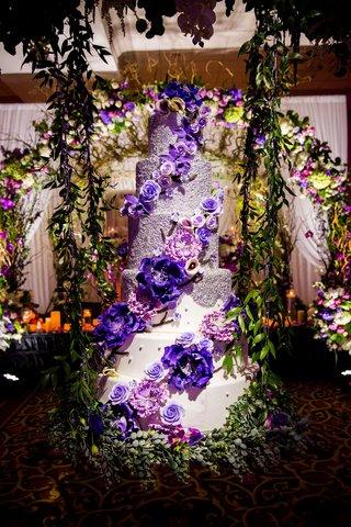 wedding-cake-six-layer-purple-flowers-white-fondant-silver-pearls-greenery-reception-ideas-swing