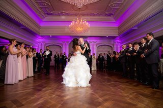 bride-in-a-strapless-lazaro-dress-with-beaded-belt-ruffled-skirt-dances-with-groom-at-park-savoy