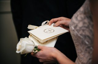 wedding-ceremony-program-being-held-by-guest-attendant-with-single-white-rose-ceremony-jobs