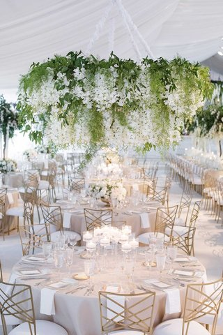 wedding-reception-white-tent-greenery-chandelier-gold-chairs-candles-low-centerpiece