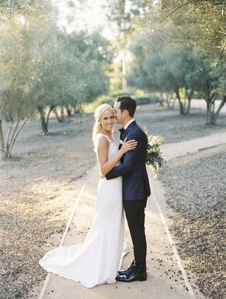 bride-in-pronovias-wedding-dress-groom-in-blue-windowpane-suit-jacket-pathway-among-trees