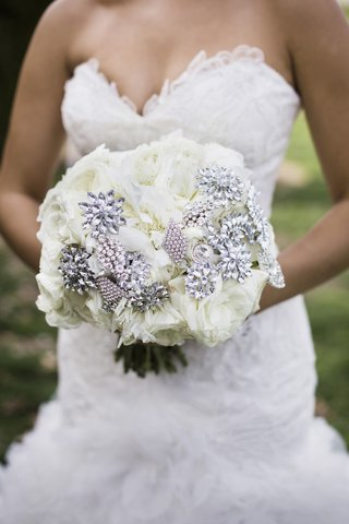 bride-in-a-strapless-mark-zunino-dress-holds-a-bouquet-of-white-flowers-with-rhinestone-brooches