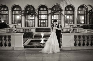 black-and-white-photo-of-bride-kissing-groom-at-wedding-anne-barge-dress-the-breakers-palm-beach