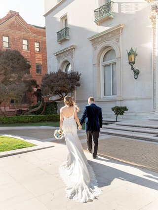 back-view-of-bride-in-pnina-tornai-holding-hands-with-groom-in-blue-velvet-jacket
