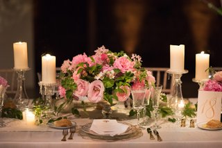 small-arrangement-of-pink-roses-and-greenery-with-pillar-candles-wedding-reception-centerpiece