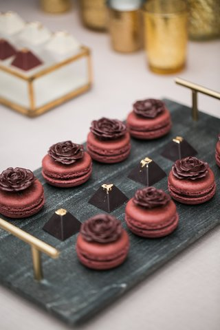 slate-tray-with-maroon-macarons-with-delicate-chocolate-roses-on-the-top-and-pyramid-truffles