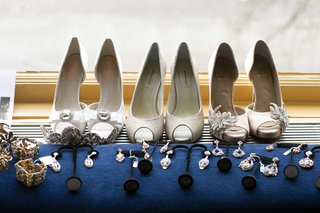 white-bridal-shoes-near-variety-of-jewelry-accessories-in-silver-and-gold