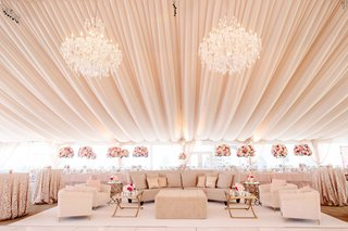 wedding-reception-tent-drapery-chandelier-lounge-area-sofa-ottoman-table-gold-pink-flowers