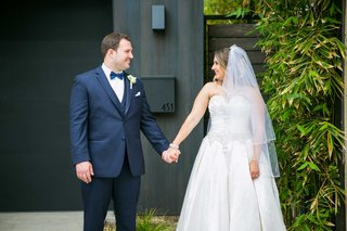 bride-in-allure-ball-gown-groom-in-navy-joseph-abboud-suit-hold-hands-and-gaze-at-each-other