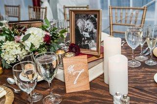 wedding-centerpieces-books-hydrangeas-framed-engagement-photos-pillar-candles