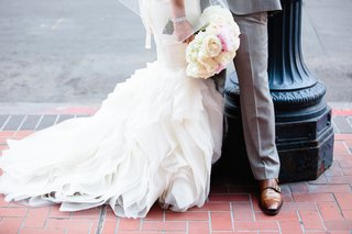 bride-in-a-vera-wang-dress-with-ruffled-skirt-and-groom-in-grey-suit-with-brown-shoes