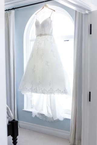 ball-gown-v-neck-wedding-dress-hanging-up-in-window-of-bridal-suite-light-blue-walls-ocean-view
