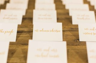 wood-wedding-table-with-white-escort-cards-gold-calligraphy-seating-assignments
