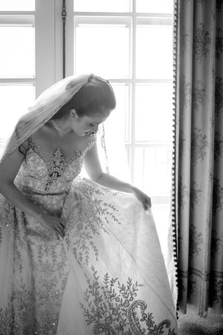 black-and-white-photo-of-bride-looking-at-detail-of-wedding-dress-from-kleinfeld-bridal-beading