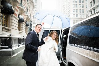 groom-holding-umbrella-for-bride-as-they-enter-snowy-wedding-car