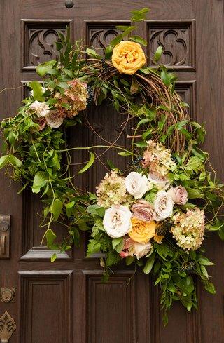 wedding-ceremony-decor-outside-door-decoration-wreath-with-greenery-white-pink-yellow-orange-flowers