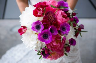 bright-bridal-bouquet-made-up-of-pink-purple-and-white-flowers-accented-by-green-foliage