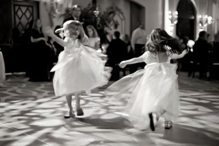 black-and-white-photo-of-flower-girls-dancing-at-a-reception