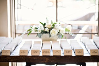 wedding-reception-escort-card-table-small-arrangement-of-white-flowers-white-place-cards-wood-table