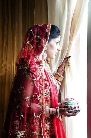 indian-bride-in-a-red-lehenga-with-a-red-embroidered-veil