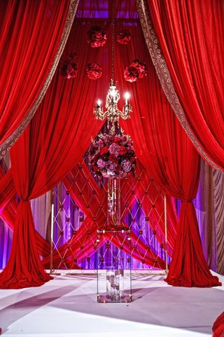 indian-ceremony-with-red-drapes-chandelier-and-red-and-purple-floral-arrangement