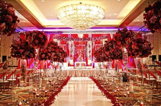 indian-wedding-ceremony-with-red-floral-arrangements-lining-the-aisle