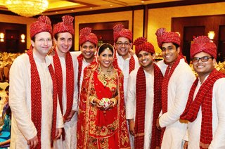 indian-bride-in-a-red-lehenga-and-veil-with-gold-and-red-embroidery-with-groomsmen-in-sherwanis