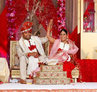 indian-bride-in-red-lehenga-and-indian-groom-in-white-sherwani-at-wedding-ceremony