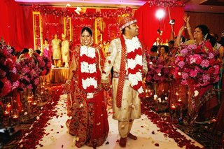 bride-in-a-red-lehenga-with-gold-embroidery-with-groom-in-gold-sherwani-with-red-embroidery