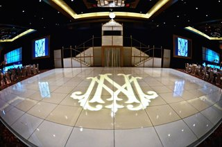 wedding-reception-with-a-glossy-tile-dance-floor-with-couples-monogram-projection
