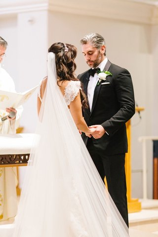 bride-with-long-hair-and-veil-pretty-straps-holding-groom-hand-during-ceremony-bow-tie-pastor-cantor