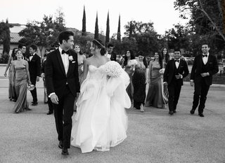 black-and-white-photo-of-bride-in-monique-lhuillier-dress-and-groom-with-wedding-party