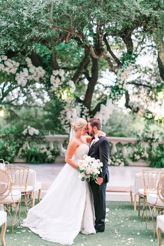bride in strapless a line wedding dress groom in tuxedo tree with white flowers gold chairs guests
